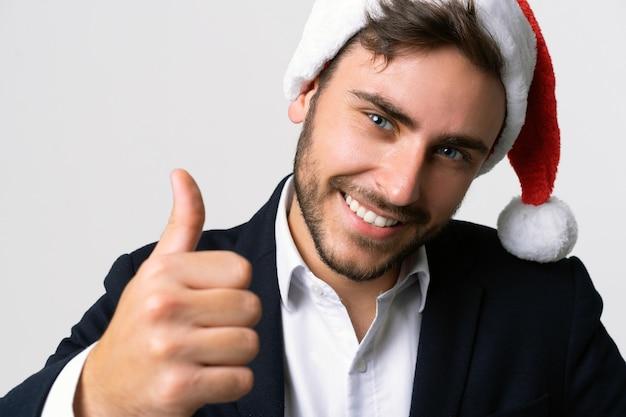 ビジネススーツとサンタ帽子が立っている若いハンサムな白人男