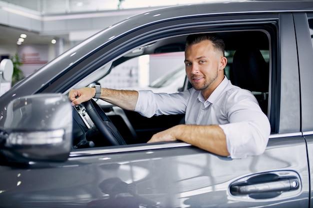 Молодой красивый кавказский парень сидит за рулем нового автомобиля