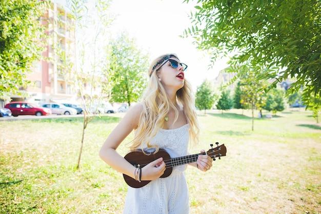 Молодая красивая кавказская длинная блондинка прямые волосы хиппи женщина городской парк
