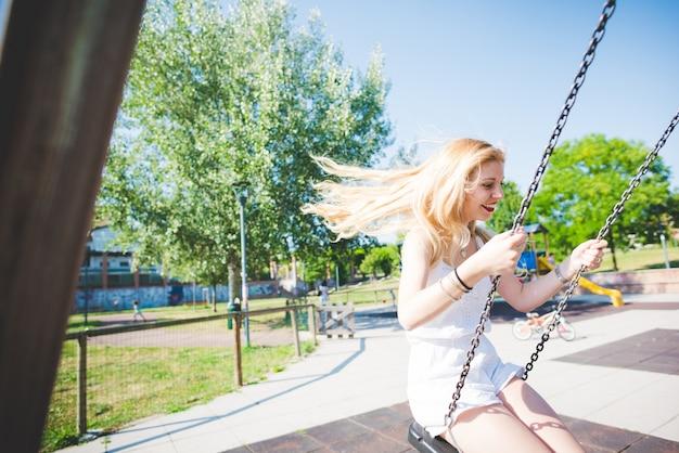 놀이터에서 그네에 재미 젊은 잘 생긴 백인 긴 금발 스트레이트 머리 여자