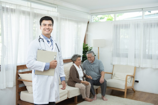 Young handsome caucasian male doctor standing hand holding document file with smile and two elderly old senior asian couple sit on couch, healthcare and medical concept.