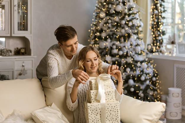 包装紙とリボンでクリスマスプレゼントを包む若いハンサムな白人男性と女性のカップル、笑顔-クリスマス、カップル、休日のコンセプト