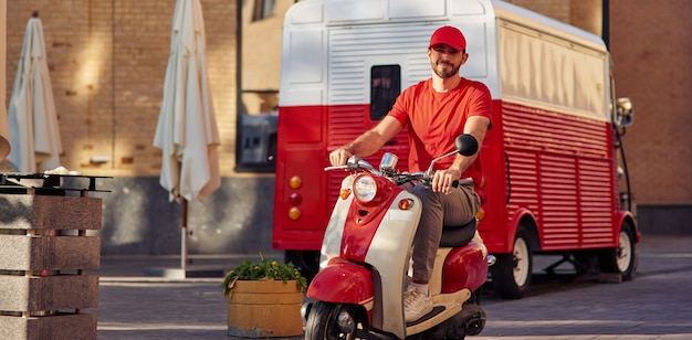 Молодой красивый кавказский курьер в красной форме за рулем скутера, улыбаясь в камеру. концепция доставки еды