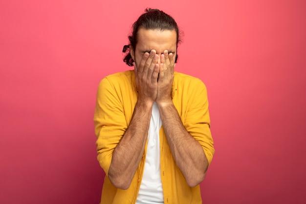 복사 공간이 진홍색 벽에 고립 된 손으로 눈을 덮고 젊은 잘 생긴 백인 남자