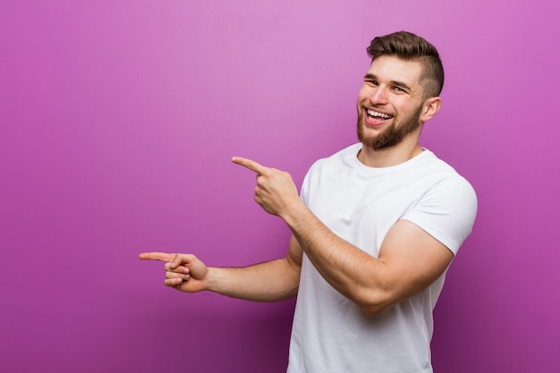 Young handsome caucasian man excited pointing with forefingers away.