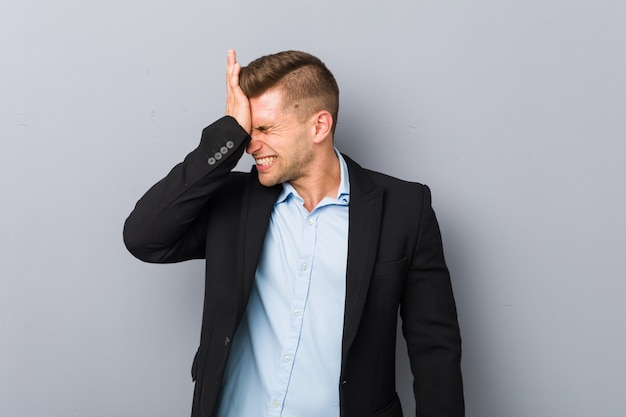 Young handsome caucasian man forgetting something, slapping forehead with palm and closing eyes.
