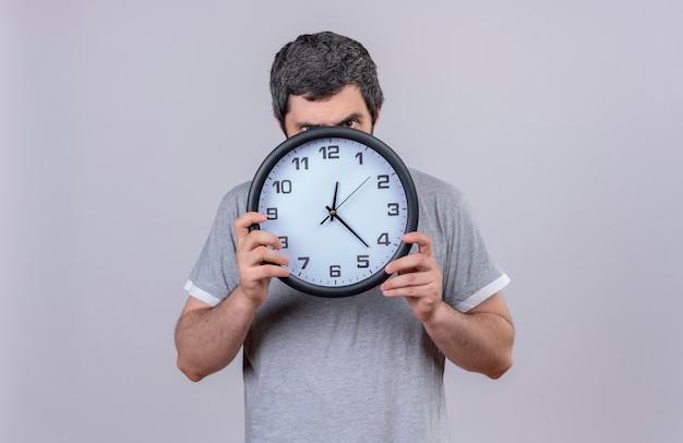 Giovane uomo caucasico bello che tiene e che guarda l'obbiettivo da dietro l'orologio isolato su priorità bassa bianca con lo spazio della copia