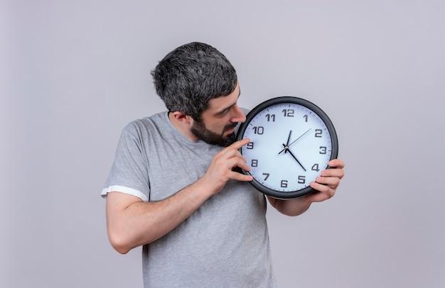 Giovane uomo caucasico bello che tiene e che guarda l'orologio isolato su priorità bassa bianca con lo spazio della copia