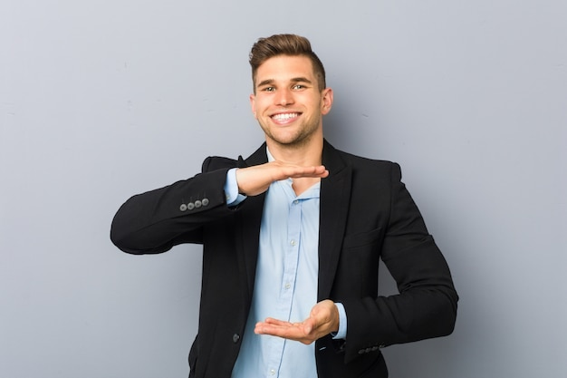 Young handsome caucasian man holding something with both hands, product presentation.