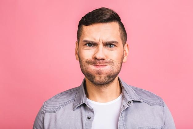 変な顔でカジュアルなふくらんでいる頬の若いハンサムな白人男性