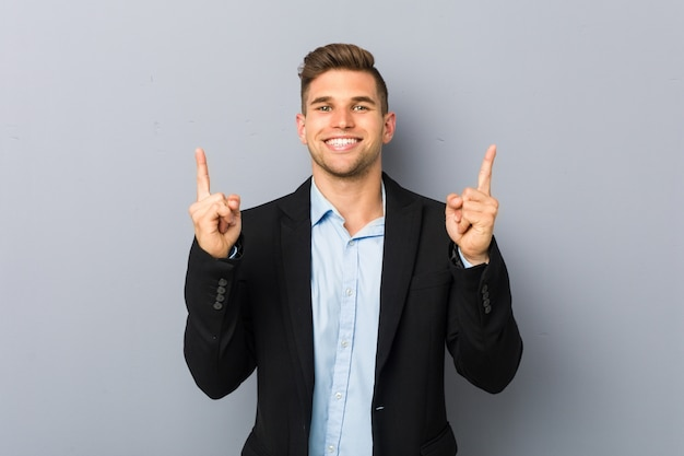 Young handsome caucasian man indicates with both fore fingers up showing a blank space.
