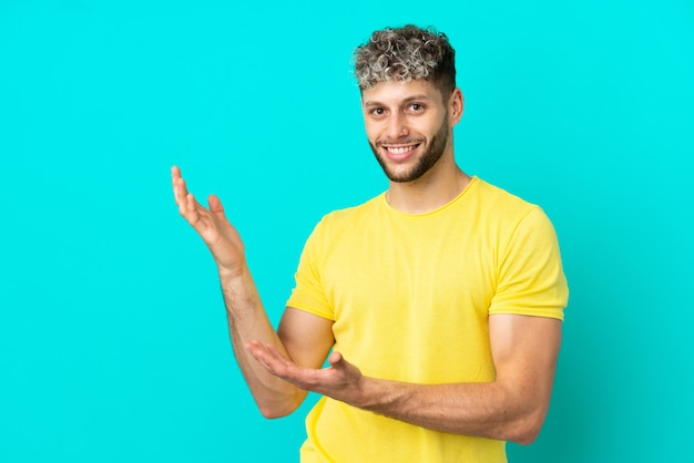 Young handsome caucasian man isolated on blue background extending hands to the side for inviting to come