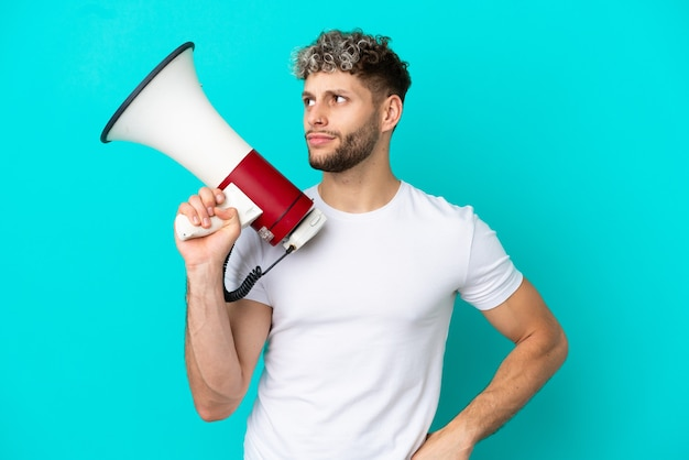 Young handsome caucasian man isolated on blue background holding a megaphone and thinking