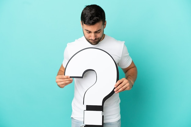 Young handsome caucasian man isolated on blue background holding a question mark icon