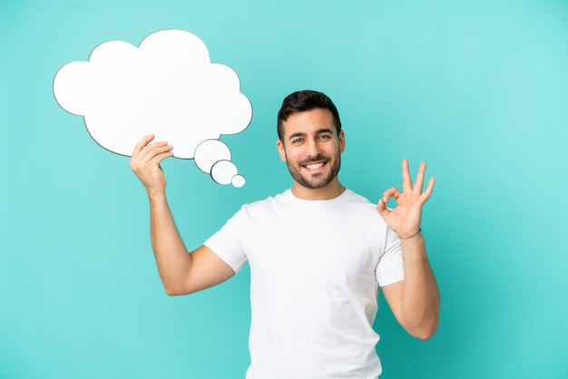 Young handsome caucasian man isolated on blue background holding a thinking speech bubble and doing ok sign