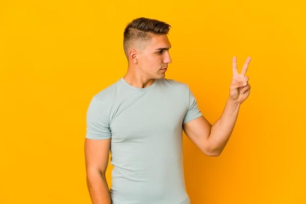 젊은 잘 생긴 백인 남자는 손가락으로 평화의 상징을 보여주는 즐겁고 평온한 고립.
