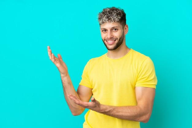 Молодой красивый кавказский мужчина изолирован на синем фоне, протягивая руки в сторону для приглашения приехать