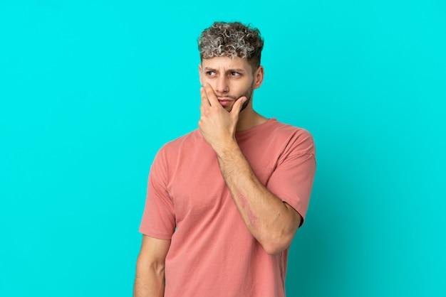 파란색 배경에 격리된 젊고 잘생긴 백인 남자는 의심을 품고 얼굴 표정을 혼란스럽게 합니다.