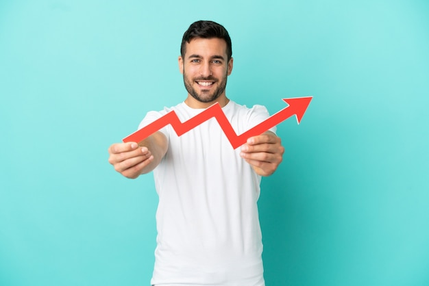 Молодой красивый кавказский мужчина изолирован на синем фоне, держа в руках ловящую восходящую стрелу с счастливым выражением лица