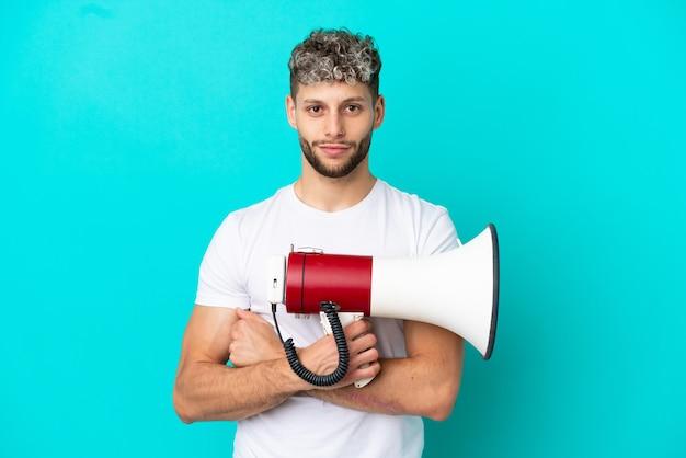 Молодой красивый кавказский мужчина, изолированные на синем фоне, держит мегафон и улыбается
