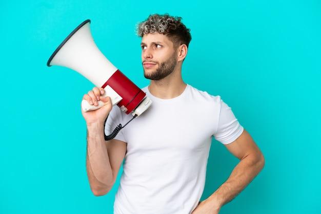Молодой красивый кавказский мужчина изолирован на синем фоне, держа мегафон и думая
