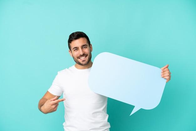 Молодой красивый кавказский мужчина изолирован на синем фоне, держа пустой речевой пузырь и указывая на него