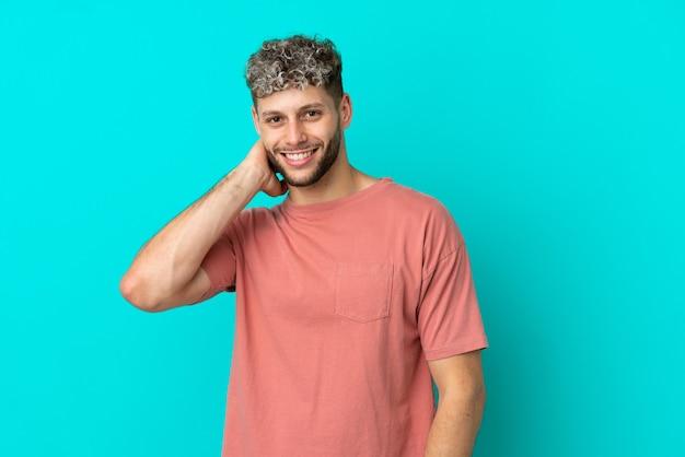 웃는 파란색 배경에 고립 된 젊은 잘생긴 백인 남자