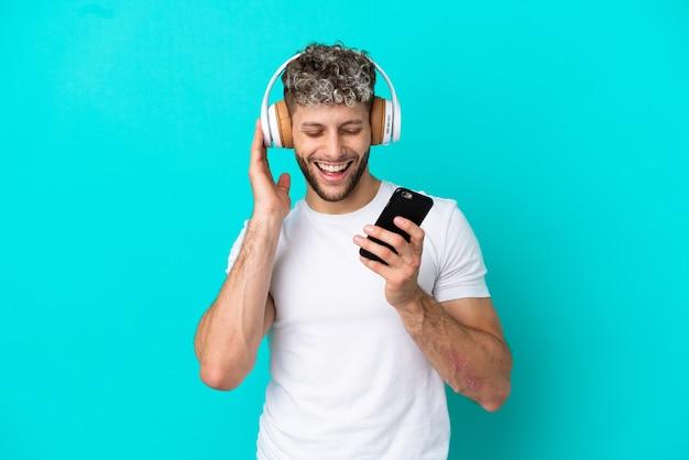 Молодой красивый кавказский мужчина изолирован на синем фоне, слушает музыку с помощью мобильного телефона и поет