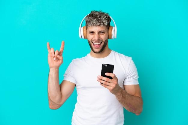 Молодой красивый кавказский мужчина изолирован на синем фоне, слушая музыку с мобильным телефоном, делая рок-жест