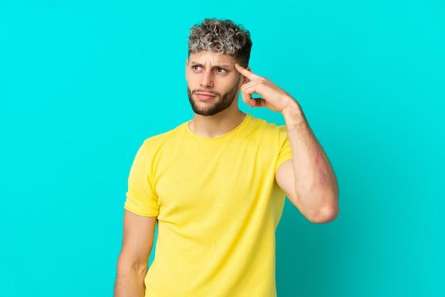 頭に指を置く狂気のジェスチャーを作る青い背景に分離された若いハンサムな白人男性