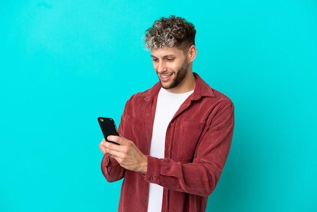 Молодой красивый кавказский мужчина изолирован на синем фоне, отправляя сообщение или электронное письмо с мобильного телефона