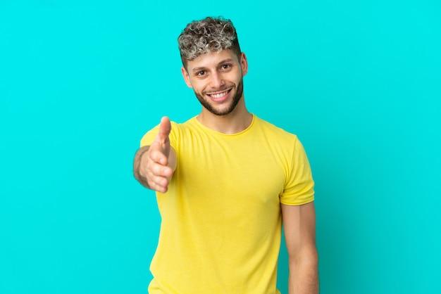Молодой красивый кавказский мужчина изолирован на синем фоне, пожимая руку для заключения хорошей сделки