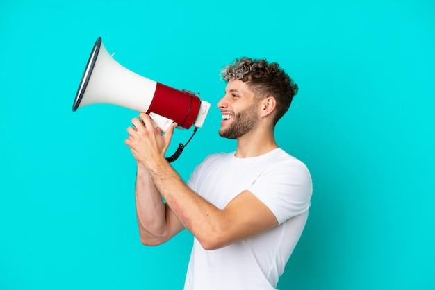 Молодой красивый кавказский мужчина изолирован на синем фоне и кричит в мегафон, чтобы объявить что-то в боковом положении