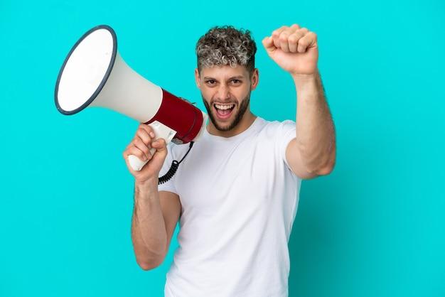 Молодой красивый кавказский мужчина, изолированные на синем фоне, кричит в мегафон, чтобы что-то объявить