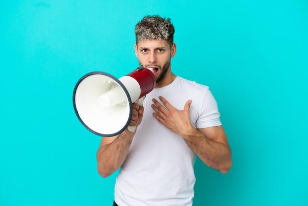 Молодой красивый кавказский мужчина изолирован на синем фоне с удивленным выражением лица кричит в мегафон