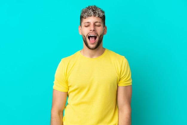 Молодой красивый кавказский мужчина изолирован на синем фоне, кричит вперед с широко открытым ртом