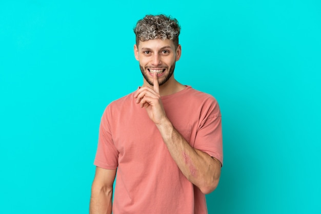 Молодой красивый кавказский мужчина изолирован на синем фоне, показывая знак жеста молчания, кладя палец в рот