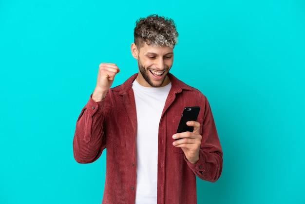 Молодой красивый кавказский мужчина изолирован на синем фоне с помощью мобильного телефона и делает жест победы
