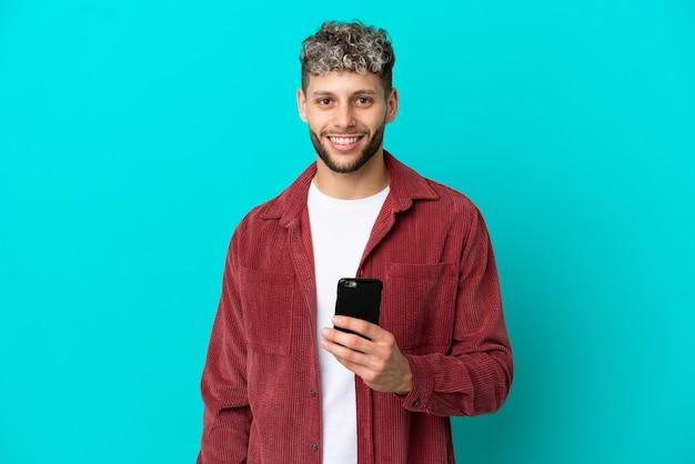 Молодой красивый кавказский мужчина изолирован на синем фоне с помощью мобильного телефона