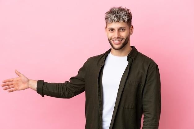 Молодой красивый кавказский мужчина изолирован на розовом фоне, протягивая руки в сторону, чтобы пригласить приехать