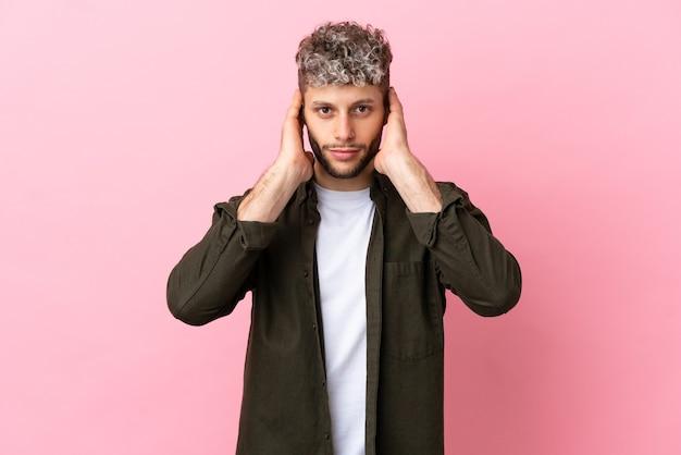 Молодой красивый кавказский мужчина изолирован на розовом фоне разочарован и закрывает уши