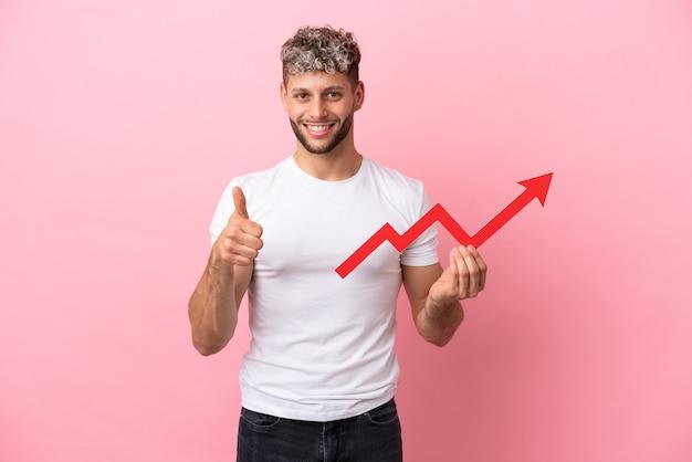 분홍색 배경에 격리된 젊고 잘생긴 백인 남자는 엄지손가락을 들고 상승 화살표를 잡고 있다