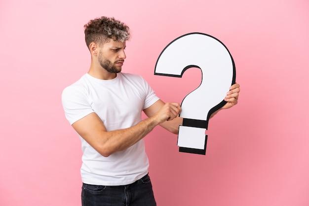 疑問符のアイコンを保持しているピンクの背景に分離された若いハンサムな白人男性