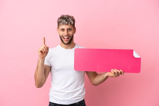 空のプラカードを保持しているピンクの背景に分離された若いハンサムな白人男性