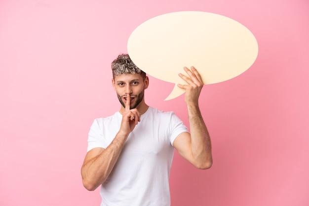 Молодой красивый кавказский мужчина изолирован на розовом фоне, держа пустой речевой пузырь и делая жест молчания