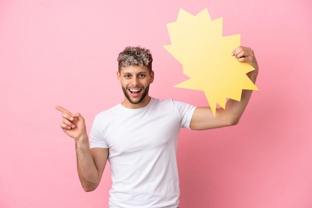 空の吹き出しを保持し、側を指すピンクの背景に分離された若いハンサムな白人男性