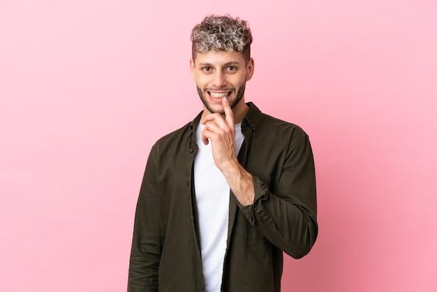 Молодой красивый кавказский мужчина изолирован на розовом фоне, показывая знак жеста молчания, кладя палец в рот