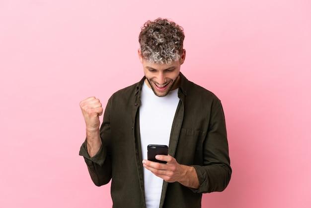 Молодой красивый кавказский мужчина изолирован на розовом фоне удивлен и отправляет сообщение