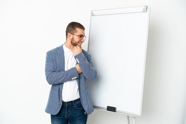 Молодой красивый кавказский мужчина изолирован на белом фоне, делая презентацию на белой доске и смотрящую сторону