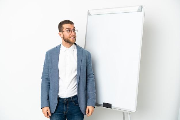 화이트 보드에 프레젠테이션을하고 웃는 동안 올려 흰색 배경에 고립 된 젊은 잘 생긴 백인 남자